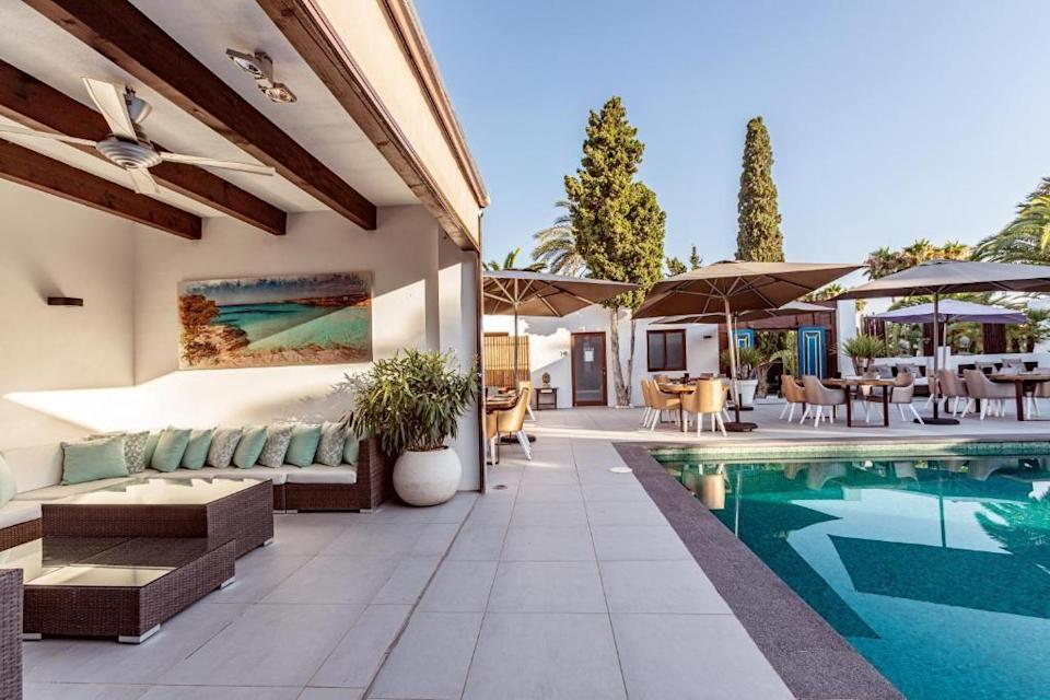 """<p>There are few places in the world where you can watch flamingos fly overhead from a sun lounger, and <a href=""""https://www.booking.com/hotel/es/casa-munich-ses-salines.en-gb.html?aid=2070929&label=ibiza-hotels"""" rel=""""nofollow noopener"""" target=""""_blank"""" data-ylk=""""slk:Casa Munich"""" class=""""link rapid-noclick-resp"""">Casa Munich</a> is by far the prettiest. A hop and a skip from Ses Salinas Nature Reserve – where you'll find some the best beaches on the island – the family-run Casa Munich has stacks of old-school Ibiza charm. From the elegant rooms and suites, all with rustic Balinese vibe, the modern glass-fronted spa to a trio of palm-fringed pools, where you can order food and cocktails to be delivered to your lounger. </p><p>Tennis courts, mountain bike hire and yoga classes (naturally) are all on offer, but there's no sit-down restaurant, however the hip beach clubs and bars of Salinas and Es Cavallet are mere moments away.</p><p><a class=""""link rapid-noclick-resp"""" href=""""https://www.booking.com/hotel/es/casa-munich-ses-salines.en-gb.html?aid=2070929&label=ibiza-hotels"""" rel=""""nofollow noopener"""" target=""""_blank"""" data-ylk=""""slk:CHECK AVAILABILITY"""">CHECK AVAILABILITY</a></p>"""