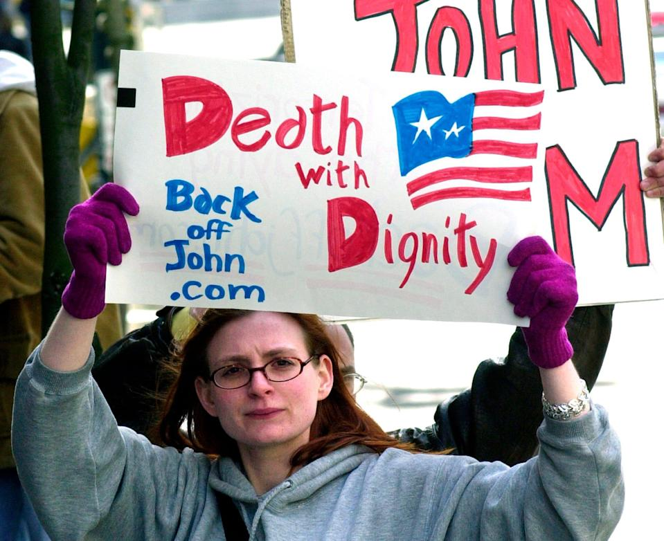 In this March 22, 2002, file photo, Stacey Richter holds a sign outside a federal courthouse in Portland, Ore., during a hearing on the fate of Oregon's physician-assisted suicide law.