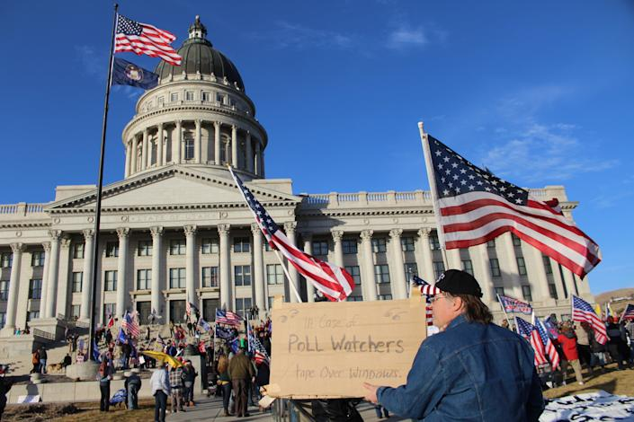 """An attendee to Salt Lake City's """"Save America"""" rally holds up a sign in front of the Utah Capitol with the message """"In case of poll watchers, tape over windows"""" on Wednesday, Jan. 6, 2021. (Enrique Limón)"""