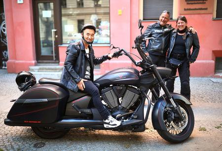Afghan migrant Ali Mohammad Rezaie poses on the motorbike of his German friends Chris and Jochen in Berlin, Germany, September 29, 2018. REUTERS/Hannibal Hanschke