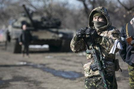 A fighter with the separatist self-proclaimed Donetsk People's Republic Army stands guard at a checkpoint along a road from Vuhlehirsk to Debaltseve in Ukraine
