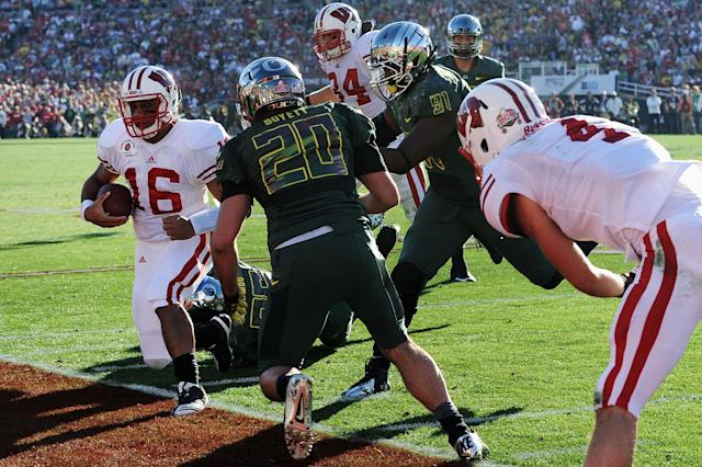 PASADENA, CA - JANUARY 02: Quarterback Russell Wilson #16 of the Wisconsin Badgers is knocked out of bounds in the second quarter against the Oregon Ducks at the 98th Rose Bowl Game on January 2, 2012 in Pasadena, California. (Photo by Harry How/Getty Images)