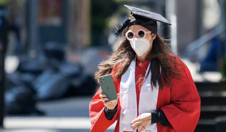A graduate wearing a mask, cap and gown amid the coronavirus pandemic on May 14, 2020 in New York City. Photo: Alexi Rosenfeld/Getty Images)