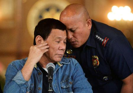 FILE PHOTO: Philippine National Police chief General Ronald Dela Rosa whispers to President Rodrigo Duterte during the announcement of the disbandment of police operations against illegal drugs at the Malacanang palace in Manila, Philippines January 29, 2017.     REUTERS/Ezra Acayan/File Photo