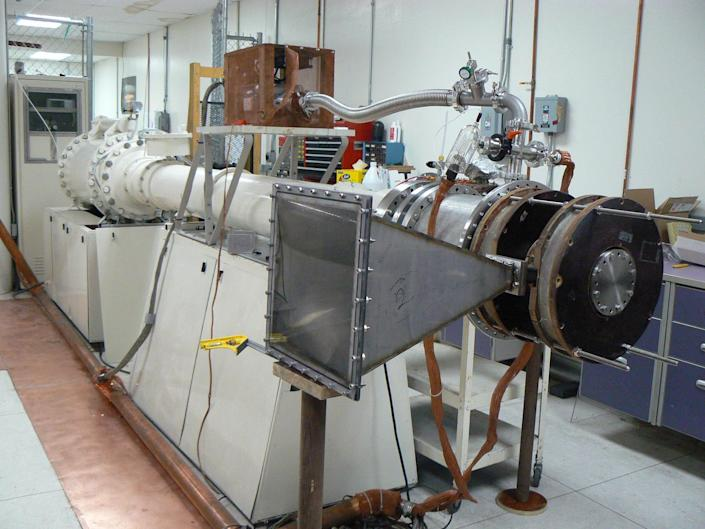 a machine in a laboratory with a rectilinear funnel-shaped structure in the foreground and a long metal pipe receding into the background