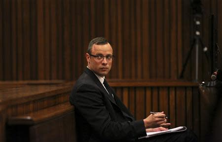 Olympic and Paralympic track star Oscar Pistorius sits in the dock during his trial for the murder of his girlfriend Reeva Steenkamp, at the North Gauteng High Court in Pretoria March 25, 2014. REUTERS/Siphiwe Sibeko/POOL