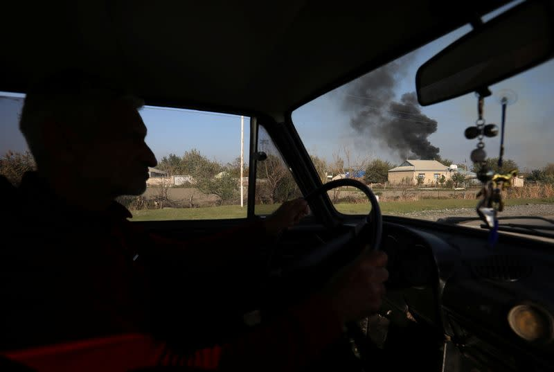 A man drives a car as smoke rises over the buildings during the fighting over the breakaway region of Nagorno-Karabakh, in Terter