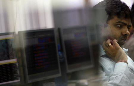 Broker looks at computer screen while trading at stock brokerage firm in Mumbai