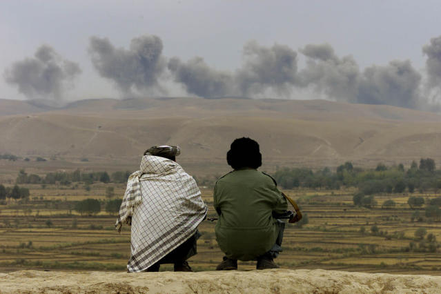 <p>Two Northern Alliance soldiers watch as the dust and smoke rises afterexplosions in Taliban positions on Kalakata hill, near the village of Ai-Khanum in northern Afghanistan, Nov. 1, 2001. (Photo: Vasily Fedosenko/Reuters) </p>