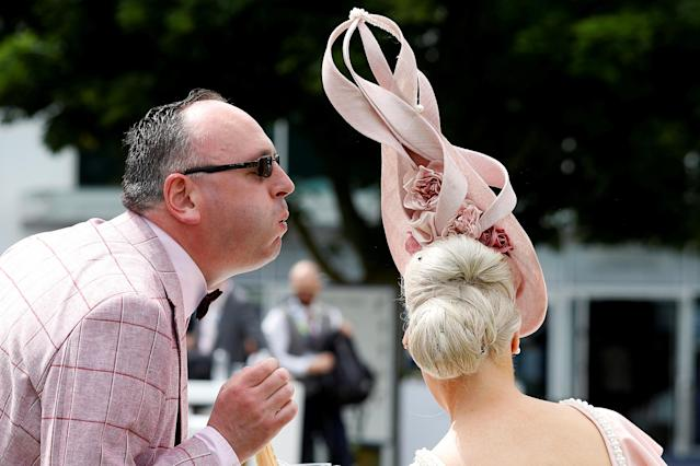 Horse Racing - Derby Festival - Epsom Downs Racecourse, Epsom, Britain - June 1, 2018 A racegoer removes an insect from a fellow racegoer's hair during Ladies Day REUTERS/Peter Nicholls TPX IMAGES OF THE DAY