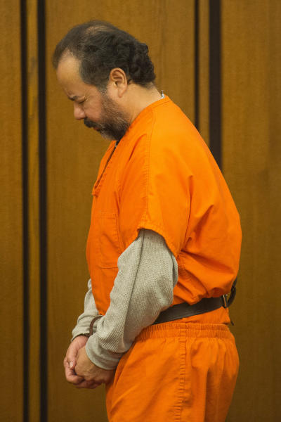 Ariel Castro, center, exits the court room after a pretrial hearing on Wednesday, June 19, 2013, in Cleveland. A tentative Aug. 4 trial date has been set for Castro, accused of kidnapping three women and holding them in his home for about a decade. (AP Photo/Jason Miller)