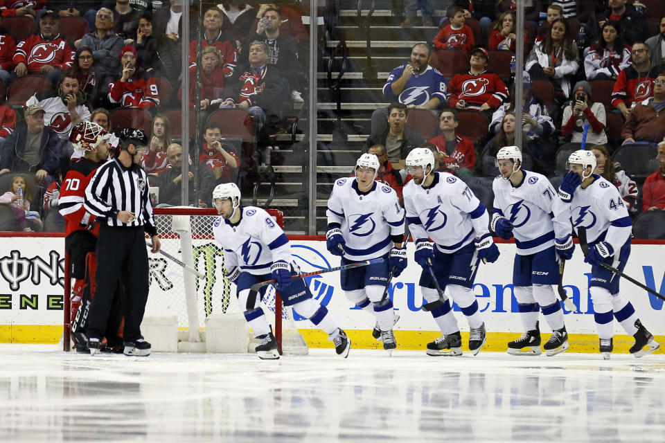 Tampa Bay Lightning center Tyler Johnson (9) skates past New Jersey Devils goaltender Louis Domingue (70) after scoring a goal during the second period of an NHL hockey game Sunday, Jan. 12, 2020, in Newark, N.J. (AP Photo/Adam Hunger)