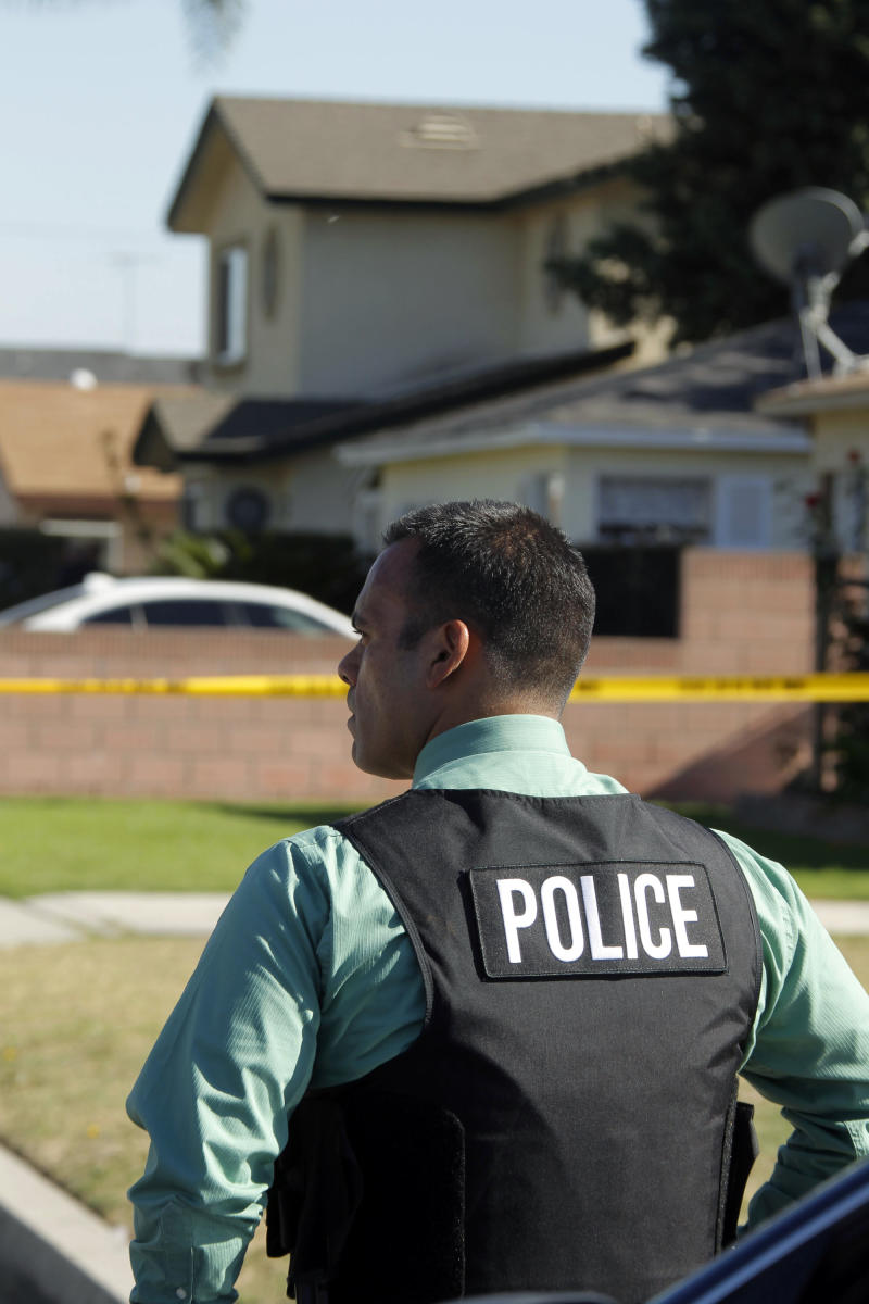 A police officer is seen down the street from the two-story home, background, where one person was found shot to death in Downey, Calif., Wednesday, Oct. 24, 2012.  Five people were shot and at least two died in shootings at a business and a residence in the Los Angeles suburb Wednesday, according to Downey police Lt. Dean Milligan.  The shootings occurred shortly after 11 a.m. at a business and at a nearby home, where family members of the business owner live. A woman was found dead at the home, he said. (AP Photo/Nick Ut)