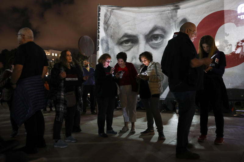 Protesters stand next to a banner showing Israeli Prime Minister Benjamin Netanyahu during rally calling for his resignation, in Tel Aviv, Israel, Saturday, Nov. 30, 2019. (AP Photo/Oded Balilty)