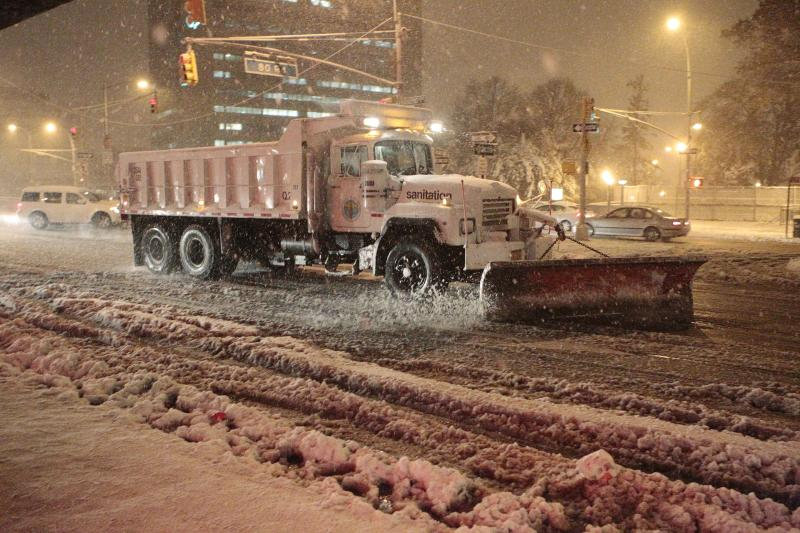 Sanitation workers shovel snow from Queens Blvd. during a snow storm Wednesday, Nov. 7, 2012, in New York. Coastal residents of New York and New Jersey faced new warnings to evacuate their homes and airlines canceled hundreds of flights as a new storm arrived Wednesday, only a week after Superstorm Sandy left dozens dead and millions without power. (AP Photo/Frank Franklin II)