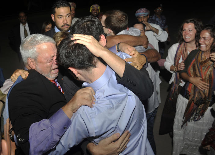 Freed American Josh Fattal, center in blue shirt, is hugged by relatives and friends upon his arrival from Iran, in Muscat, Oman Wednesday, Sept. 21, 2011. After more than two years in Iranian custody, two Americans convicted as spies took their first steps toward home Wednesday as they bounded down from a private jet and into the arms of family for a joyful reunion in the Gulf state of Oman. (AP Photo/Sultan Al-Hasani)