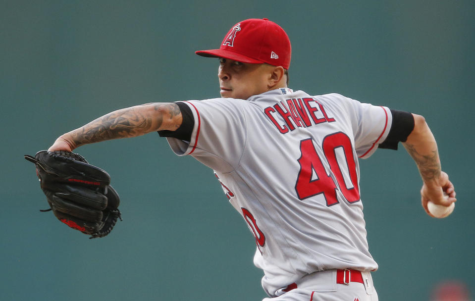 FILE - Los Angeles Angels starting pitcher Jesse Chavez winds up during the first inning of the team's baseball game against the Cleveland Indians in Cleveland, in this Tuesday, July 25, 2017, file photo. Veteran right-hander Jesse Chavez has re-signed with the Los Angeles Angels on a minor league deal. Chavez will join the Angels' spring training camp in Tempe, Arizona, after he clears their intake protocols. (AP Photo/Ron Schwane, File)