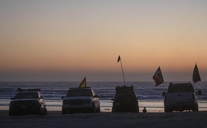 Trucks sporting flags parked on the beach with the ocean behind