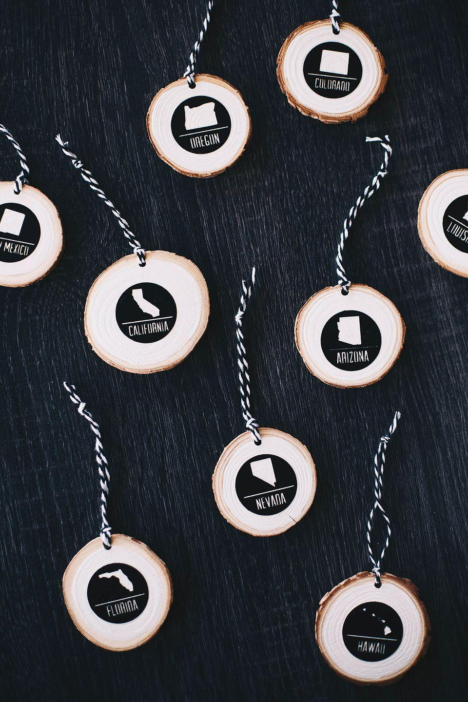 """<p>Celebrate your family's travels with these ornaments that have painted state decals on each wood slice. We think these also make the perfect gift for friends or family who travel often—and it doesn't have to be limited to states!</p><p><strong>Get the tutorial at <a href=""""https://allforthememories.com/sponsored-easing-in-to-the-holiday-decor-diy-modern-travel-ornament/"""" rel=""""nofollow noopener"""" target=""""_blank"""" data-ylk=""""slk:All for the Memories"""" class=""""link rapid-noclick-resp"""">All for the Memories</a>.</strong></p><p><strong><a class=""""link rapid-noclick-resp"""" href=""""https://www.amazon.com/Fuyit-Unfinished-Predrilled-Christmas-Ornaments/dp/B078HB4ZD7/ref=sr_1_4?tag=syn-yahoo-20&ascsubtag=%5Bartid%7C10050.g.1070%5Bsrc%7Cyahoo-us"""" rel=""""nofollow noopener"""" target=""""_blank"""" data-ylk=""""slk:SHOP WOOD SLICES"""">SHOP WOOD SLICES</a><br></strong></p>"""
