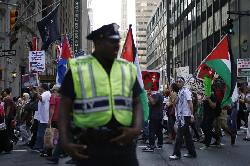 A NYPD officer stands guard while Palestinians take part in a protest in New York
