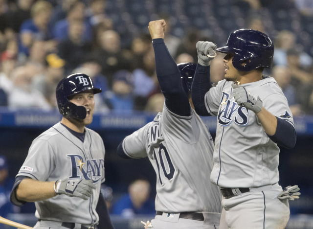 Tampa Bay Rays' Willy Adames, right, celebrates with Mike Zunino, center and another teammate after hitting two-run home run against the Toronto Blue Jays during the ninth inning of a baseball game Friday, April 12, 2019, in Toronto. (Fred Thornhill/The Canadian Press via AP)