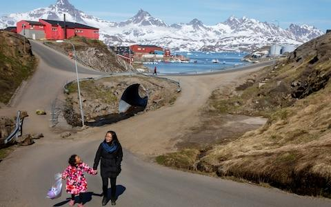 <span>A woman and child hold hands as they walk on the street in the town of Tasiilaq, Greenland</span> <span>Credit: Lucas Jackson/Reuters </span>