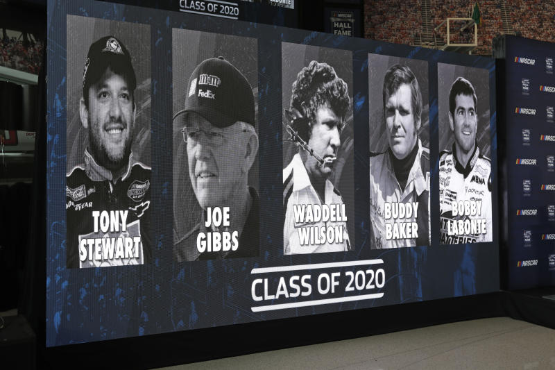 Images of NASCAR's Hall of Fame Class of 2020, from left, Tony Stewart, Joe Gibbs, Waddell Wilson, Buddy Baker and Bobby Labonte are shown on a screen after an announcement in Charlotte, N.C., Wednesday, May 22, 2019. (AP Photo/Chuck Burton)