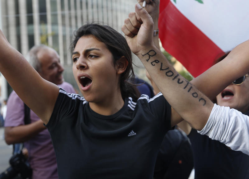 An anti-government protester shots slogans after she was attacked by Hezbollah supporters, in Beirut, Lebanon, Tuesday, Oct. 29, 2019. Lebanon's prime minister resigned, bowing to one of the central demands of the protesters. The news came shortly after baton-wielding Hezbollah supporters rampaged through the main protest camp in Beirut, torching tents and chasing away demonstrators. (AP Photo/Hussein Malla)
