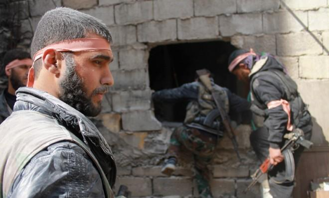 Free Syrian Army fighters move through a hole in a wall during an infiltration operation, April 22.