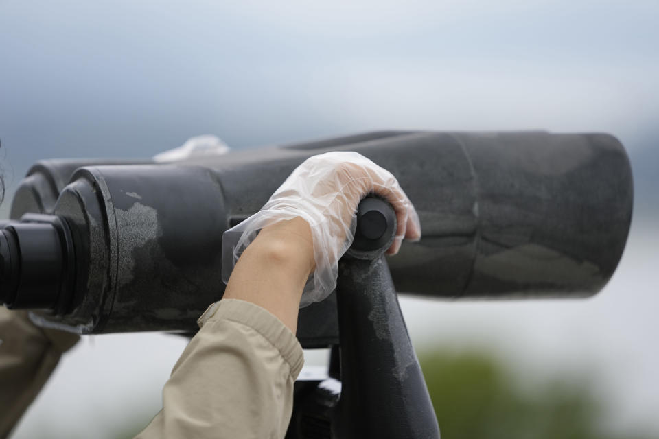 A visitor wearing plastic gloves to help protect against the spread of the coronavirus holds binoculars to see the North Korean side from the unification observatory in Paju, South Korea, Tuesday, Sept. 28, 2021. (AP Photo/Lee Jin-man)
