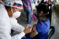 FILE - In this April 23, 2021, file photo, a health care worker inoculates Dr. Virma Rivas with the Sputnik V COVID-19 vaccine, as part of a vaccination campaign in Tegucigalpa, Honduras. Honduras has obtained a paltry 59,000 vaccine doses for its 10 million people. Similar gaps in vaccine access are found across Africa, where just 36 million doses have been acquired for the continent's 1.3 billion people, as well as in parts of Asia. (AP Photo/Elmer Martinez, File)