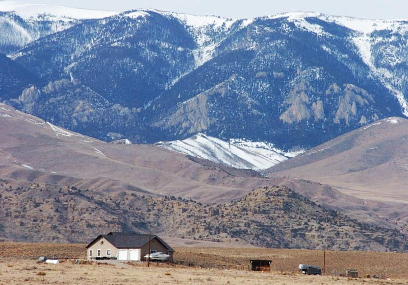The Beartooth Mountains rise up behind a house in Clark, Wyo., Tuesday, March 5, 2013, where a woman and her parents where killed during an alleged vehicle theft. The violence has tested residents' perceptions of safety in the rural, agriculture-centered community. (AP Photo/Matthew Brown)