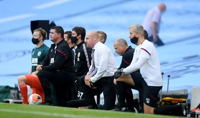 Burnley manager Sean Dyche and his staff take a knee before the Manchester City game (Michael Regan/NMC Pool/PA).