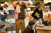 Rob Lowe (L) sighs while searching through donated clothing at an encampment for fire evacuees at a Walmart parking lot in Chico, California