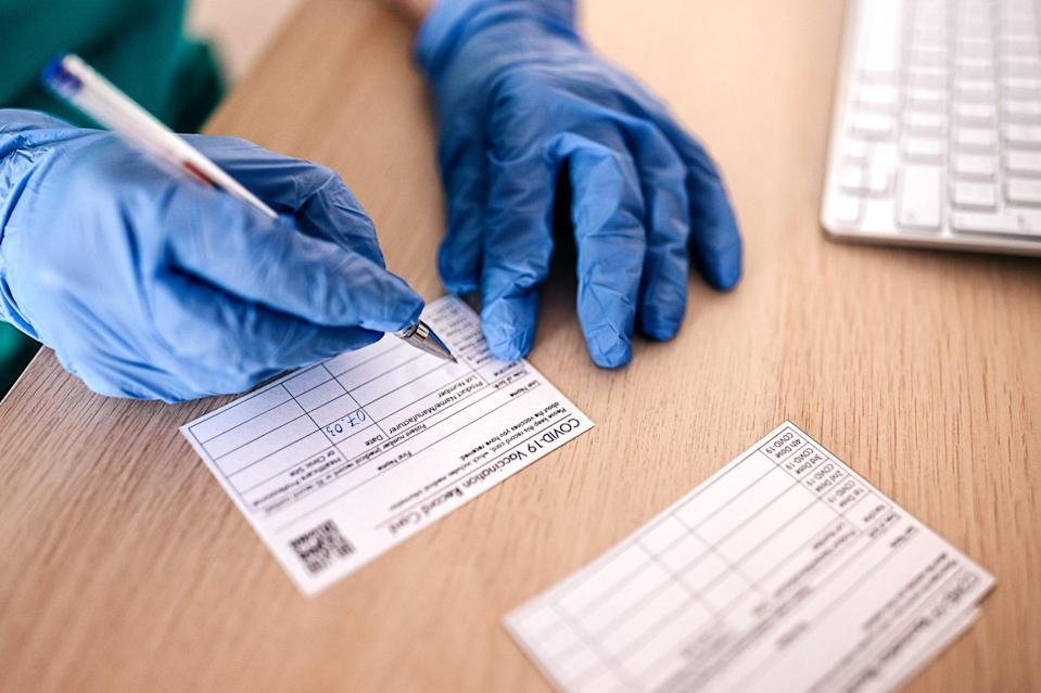 doctor filling in covid-19 vaccine card