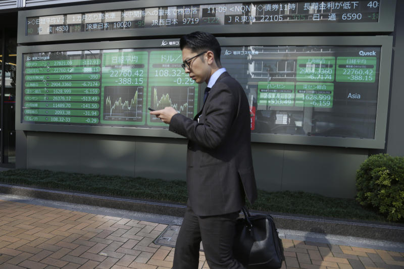 In this Thursday, Nov. 21, 2019, photo, a man walks by an electronic stock board of a securities firm in Tokyo. Stocks logged modest gains Friday, Nov. 22, 2019, in Asia after a lackluster overnight session on Wall Street ended with the market's third straight drop. (AP Photo/Koji Sasahara)