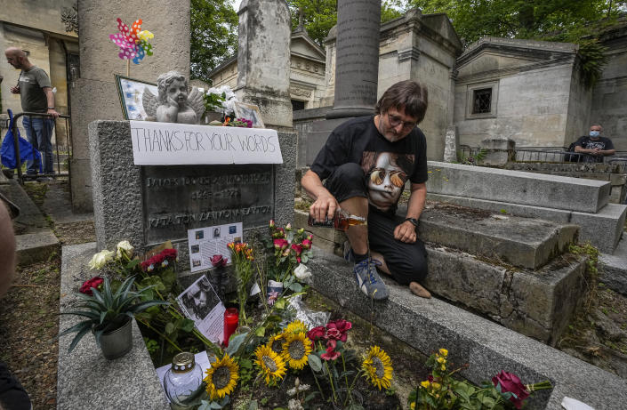 Torsten Marquardt of Germany pours some whiskey on the tomb of rock singer Jim Morrison at the Pere-Lachaise cemetery in Paris, Saturday, July 3, 2021. Fans across Europe gathered at the grave of rock legend Jim Morrison to mark the 50th anniversary of his death. (AP Photo/Michel Euler)