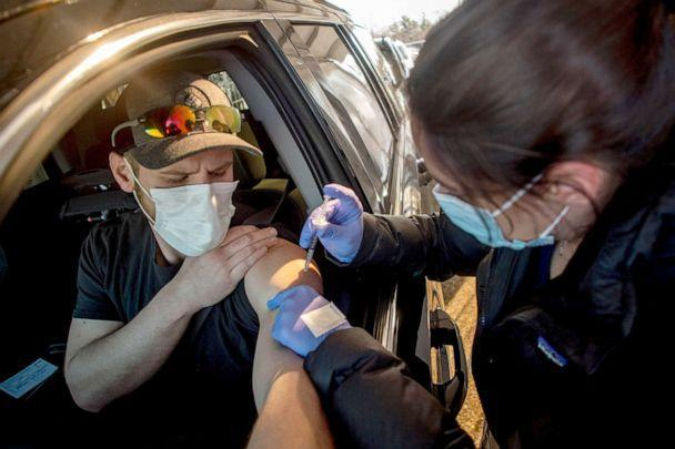 PHOTO: UM-Flint nursing student Michaela Dimello gives Burton resident John Ray his first dose of the Moderna COVID-19 vaccine at Bishop Airport in Flint, Mich., March 29, 2021. (Jake May/AP)