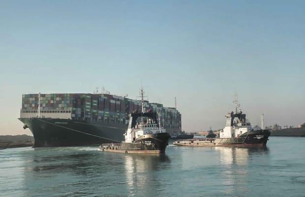 In this photo released by Suez Canal Authority, the Ever Given is seen being pulled by tugboats in the canal on March 29. Two Robert Allan-designed tugboats can be seen in the background. (AP - image credit)