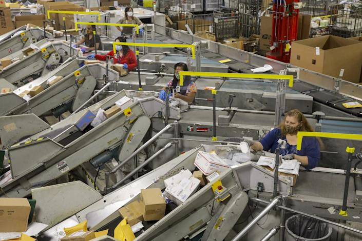Packages move through large metal conveyor machines with a postal worker at each machine
