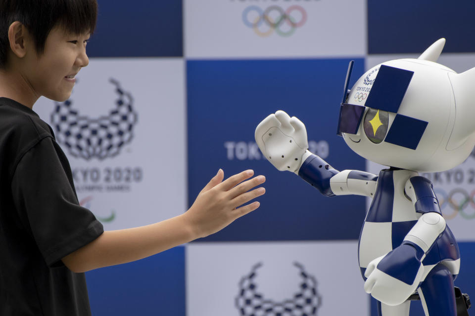 A boy shakes hands with Tokyo 2020 mascot robot Miraitowa at Tokyo Stadiuam in Chofu, on the outskirts of Tokyo, Japan, 22 July 2019. The ceremony took place prior to the 'One Year To Go Tokyo 2020' ceremony on 24 July 2019. The Tokyo 2020 Olympics will take place from 24 July 2020 through 09 August 2020. The Tokyo 2020 Organising Committee of the Olympic and Paralympic Games unveiled the mascot robot Miraitowa, developed by Toyota Motor Corp. (Photo by Alessandro Di Ciommo/NurPhoto via Getty Images)