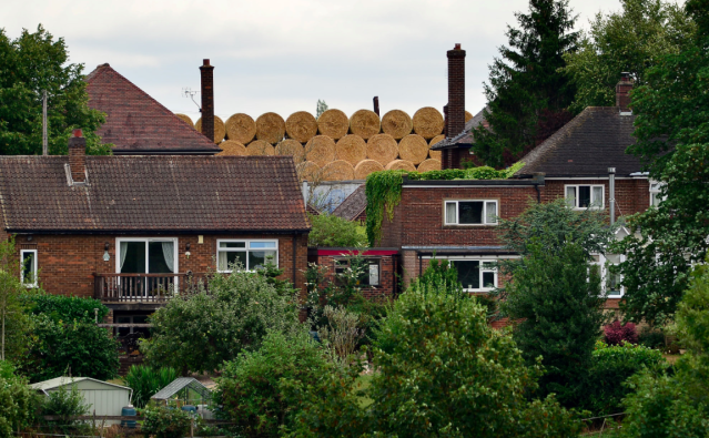 <em>The hay blocks out the view of the fields behind the houses (SWNS)</em>