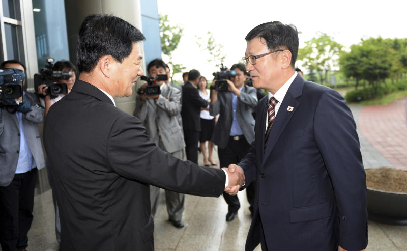 Suh Ho, the head of South Korea's working-level delegation, right, shakes hands with his North Korean counterpart Park Chol Su upon his arrival for a meeting between the two Koreas at Kaesong Industrial District Management Committee in Kaesong, North Korea, Wednesday, July 10, 2013. They met to discuss how to restart a shuttered factory complex that had been run by both Koreas until its shutdown in April. (AP Photo/Korea Pool vis Yonhap) KOREA OUT
