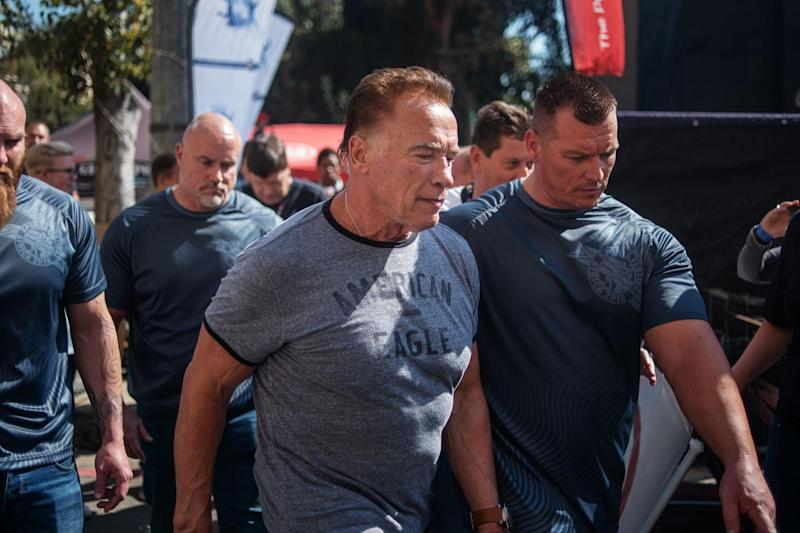 Shocking moment Arnold Schwarzenegger is drop-kicked from behind while posing for selfies at public event