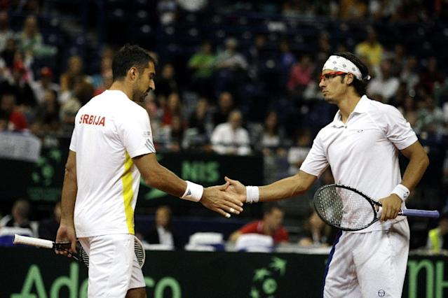 Serbia's Nenad Zimonjic, left, and Ilija Bozoljac celebrate a point during their Davis Cup semifinal tennis doubles match against Canada's Daniel Nestor and Vasek Pospisil in Belgrade, Serbia, Saturday, Sept. 14, 2013. (AP Photo/Marko Drobnjakovic)