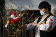 A woman wearing a face mask places knitted flowers in a bush during a spring charms fair at the Dimitrie Gusti Village Museum Museum in Bucharest, Romania, Feb. 27, 2021. Millions of East Europeans celebrate the arrival of spring on March 1 with charms tied with red-and-white string, a centuries-old custom symbolizing hope and a new season. (AP Photo/Vadim Ghirda)