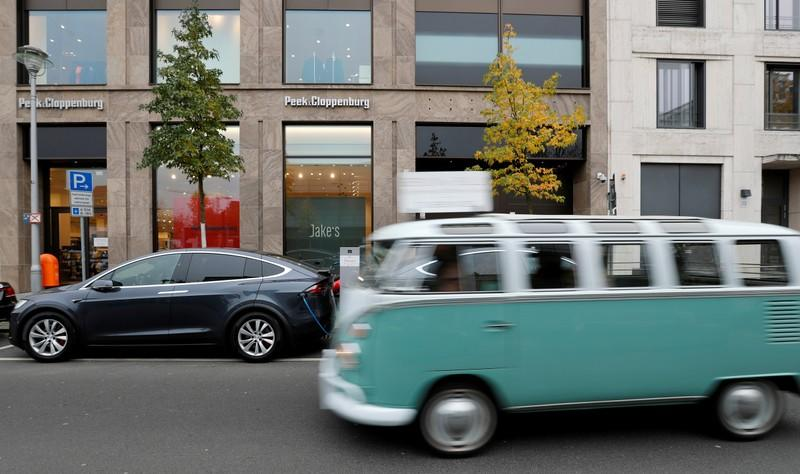 A Volkswagen oldtimer car drives past a Tesla Model X electric car recharging batteries in Berlin