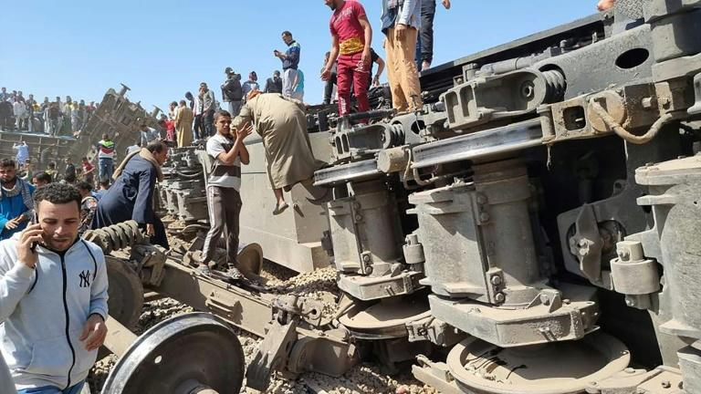 Rescuers gather around the overturned wreckage of two passenger trains that collided in the Tahta district of southern Egypt, killing at least 32 people