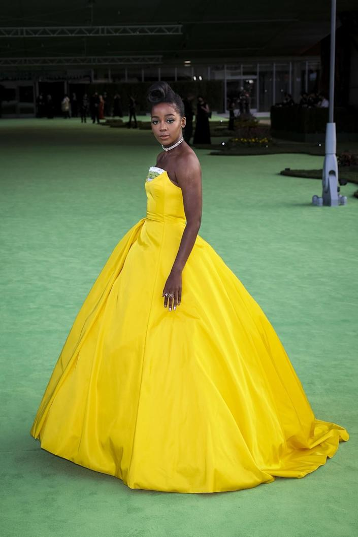 A woman in a yellow dress posing on a green carpet