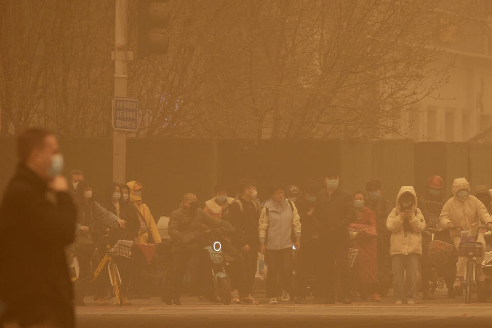 People wait to cross an intersection amid a sandstorm during the morning rush hour in Beijing. (AP Photo/Mark Schiefelbein)